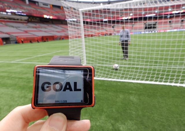 Imagem com um relógio e  um gol de fundo, Ilustrando o funcionamento do goal-line.